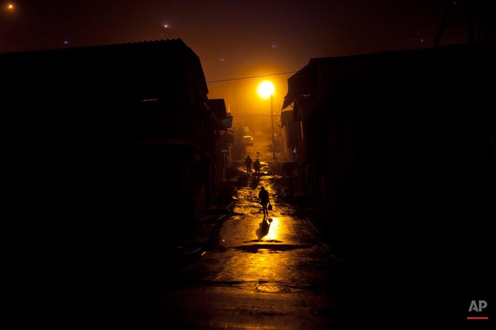 People walk through a mud street in Villa Maria del Triunfo district, Lima, Peru, Wednesday, July 24, 2013. (AP Photo/Rodrigo Abd)