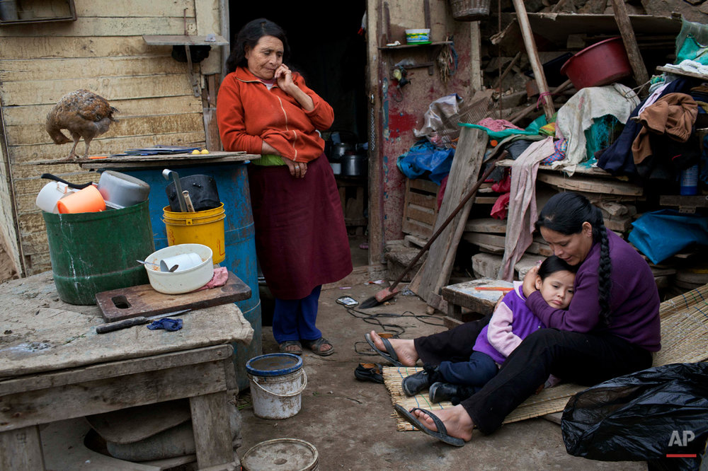 Maria Esperanza Vargas Lopez, 28, embraces her daughter Saomi, 5, as they gather in their house with her mother Felicita Lopez in the Vista Alegre neighborhood in Lima, Peru, Thursday, July 25, 2013. (AP Photo/Rodrigo Abd)