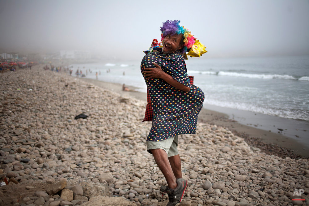 Eduardo, a street vendor who sells snacks to beach goers, strikes a pose on the shore of La Herradura beach in Lima, Peru, Saturday, March 15, 2014. Some street vendors in Lima will dress to achieve a voluptuous body type using balloons and banter with potential customers to attract attention, in hopes of increasing their sales. (AP Photo/Rodrigo Abd)