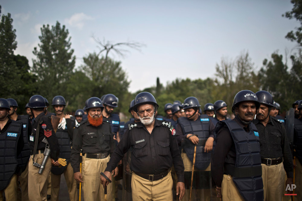 Pakistani police officers stand guard near the Parliament building after tens of thousands of protesters entered Islamabad's high-security Red Zone the night before, five days after arriving in the capital from the eastern city of Lahore in convoys, in Islamabad, Pakistan, Wednesday, Aug. 20, 2014. Pakistani lawmakers met Wednesday as tens of thousands of protesters thronged outside the assembly calling for the resignation of Prime Minister Nawaz Sharif over alleged voting fraud. (AP Photo/Muhammed Muheisen)