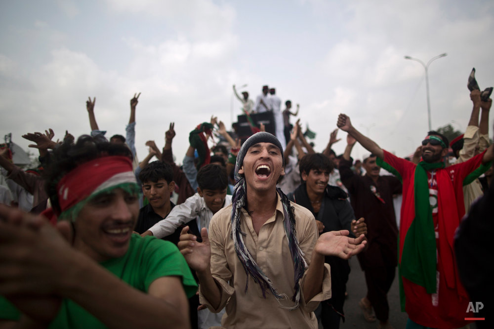 Supporters of Pakistan's cricketer-turned-politician Imran Khan, chant slogans, while waiting for other supporters marching to Islamabad from Lahore, in Islamabad, Pakistan, Friday, Aug. 15, 2014. Thousands of opposition protesters on Thursday joined large convoys headed to Pakistan's capital Islamabad for a mass rally to demand the ouster of the prime minister over allegations of vote fraud.  (AP Photo/Muhammed Muheisen)