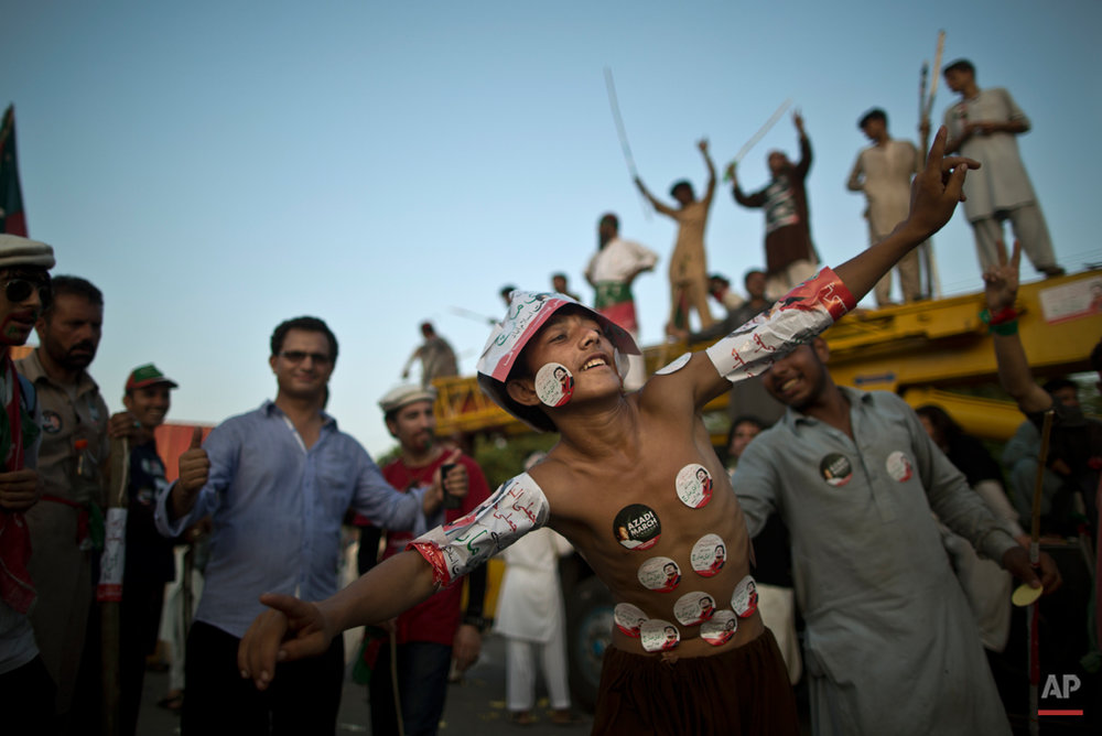 A young supporter of Pakistani cricketer-turned-politician Imran Khan, his body decorated with stickers showing Khan, dances with others during a protest in Islamabad, Pakistan, Tuesday, Aug. 19, 2014. Khan on Monday announced to lead thousands of anti-government protesters into the high security ëRed Zoneí as his 48 hours deadline for government to step down ending Tuesday. (AP Photo/Muhammed Muheisen)