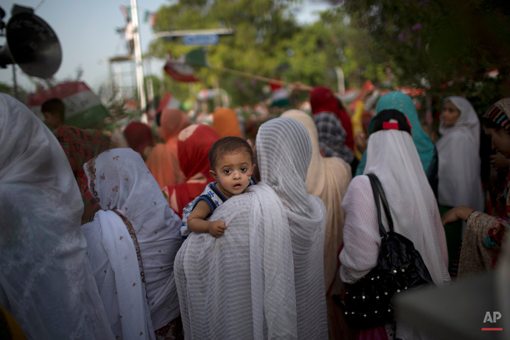 A supporter of fiery anti-government cleric Tahir-ul-Qadri, holds her child, while she and other protestors listen to his speech during a protest in Islamabad, Pakistan, Monday, Aug. 18, 2014. Qadri led massive rallies Saturday in Pakistanís capital, demanding Prime Minister Nawaz Sharif step down over alleged fraud in last yearís election in front of thousands of protesters. (AP Photo/Muhammed Muheisen)