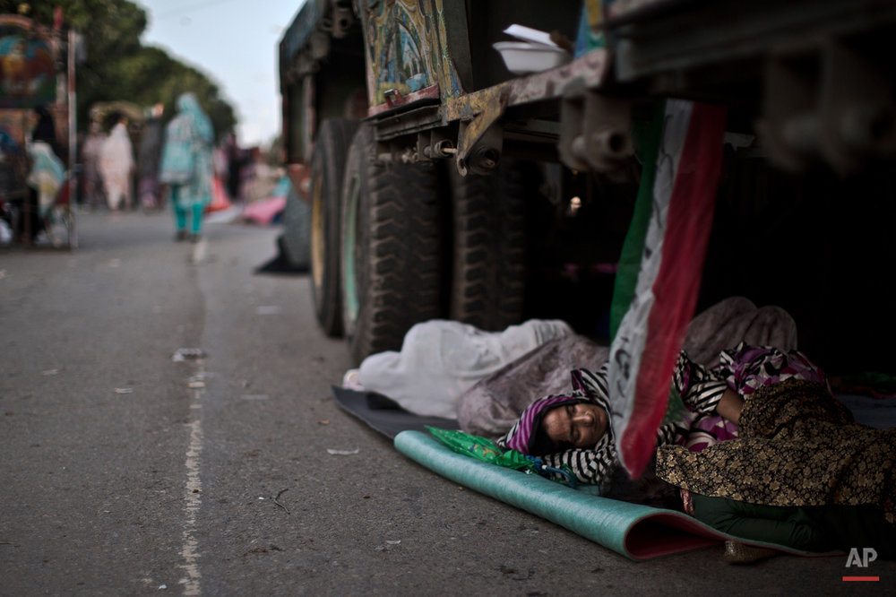 A supporter of anti-government cleric Tahir-ul-Qadri, sleeps on the ground under a truck, during a protest, in Islamabad, Pakistan, Sunday, Aug. 17, 2014. Qadri led massive rallies Saturday in Pakistan'??s capital, demanding Prime Minister Nawaz Sharif step down over alleged fraud in last year'??s election in front of thousands of protesters. (AP Photo/Muhammed Muheisen)