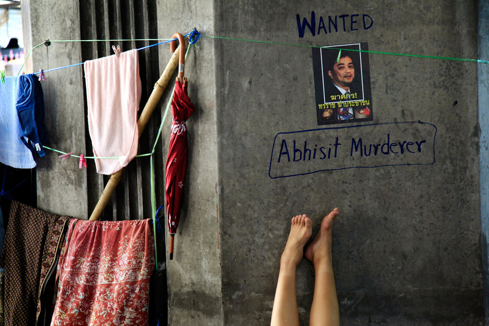 A woman sleeps under a defaced poster with a picture of Thailand's Prime Minister Abhisit Vejjajiva in the anti-government encampment on Monday May 10, 2010 in Bangkok, Thailand. Thailand's prime minister pleaded Sunday for an end to two months of street protests paralyzing part of the capital and an acceptance of his reconciliation plan that has been stalled by fresh violence. (AP Photo/Wong Maye-E)