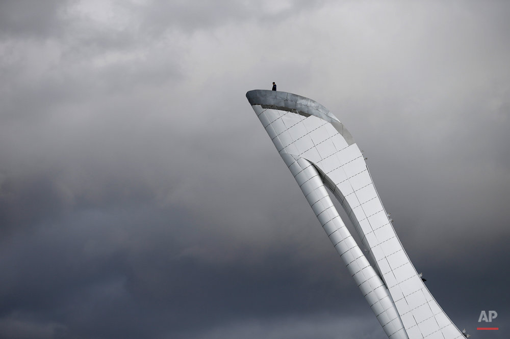 A worker is dwarfed against the sky as he stands at the top of the Olympic cauldron ahead of the 2014 Winter Olympics, Tuesday, Feb. 4, 2014, in Sochi, Russia. (AP Photo/Wong Maye-E)