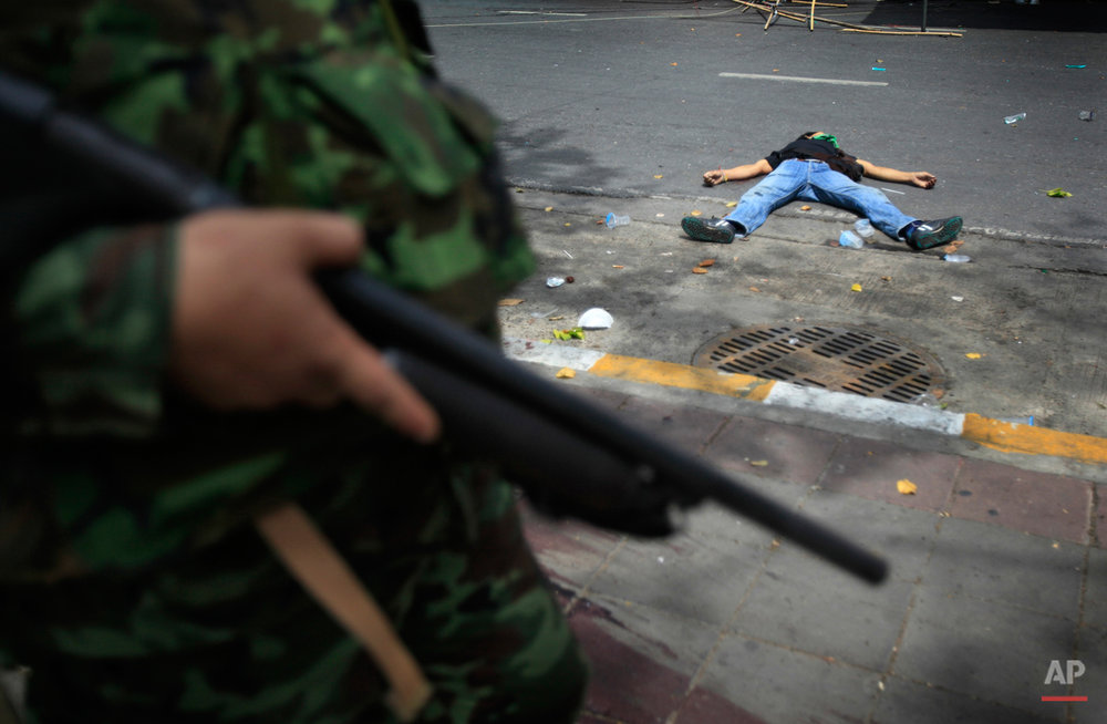 Thai soldiers storm into anti-government protesters' encampment while a protester lies dead on Wednesday May 19, 2010, in Bangkok, Thailand. Downtown Bangkok became a raging battleground Wednesday as the army stormed a barricaded protest camp and the Red Shirt leadership surrendered, enraging demonstrators who fired grenades and set fires that cloaked the skyline in a black haze. (AP Photo/Wong Maye-E )
