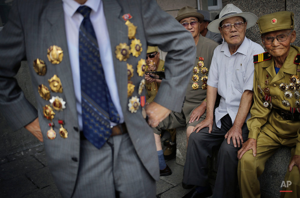 North Korean war veteran, Kim Hak Chol, 81, a retired soldier, right, together with other veterans decorated with medals, attend a parade to celebrate the anniversary of the  Korean War armistice agreement, Sunday, July 27, 2014, in Pyongyang, North Korea. North Koreans gathered at Kim Il Sung Square as part of celebrations for the 61st anniversary of the armistice that ended the Korean War.  (AP Photo/Wong Maye-E)