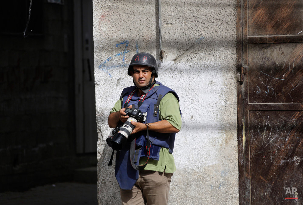 In this Saturday, Aug. 2, 2014 photo, Associated Press photographer Hatem Moussa works, in Gaza City, Gaza Strip. (AP Photo/Lefteris Pitarakis)