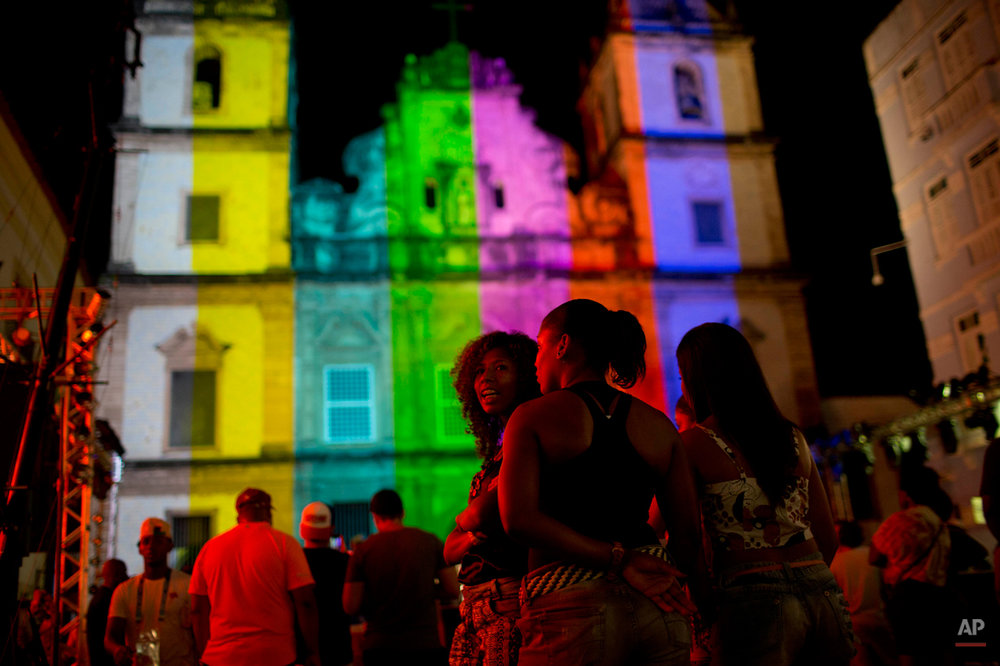 Girls gather in front of San Francisco Church, in Pelourinho neighborhood, near the Arena Fonte Nova stadium in Salvador, Brazil, where US an Belgium played a World Cup round of 16 match, Tuesday, July 1, 2014. The church is being illuminated in different colors in preparation for a concert on Wednesday. (AP Photo/Rodrigo Abd)
