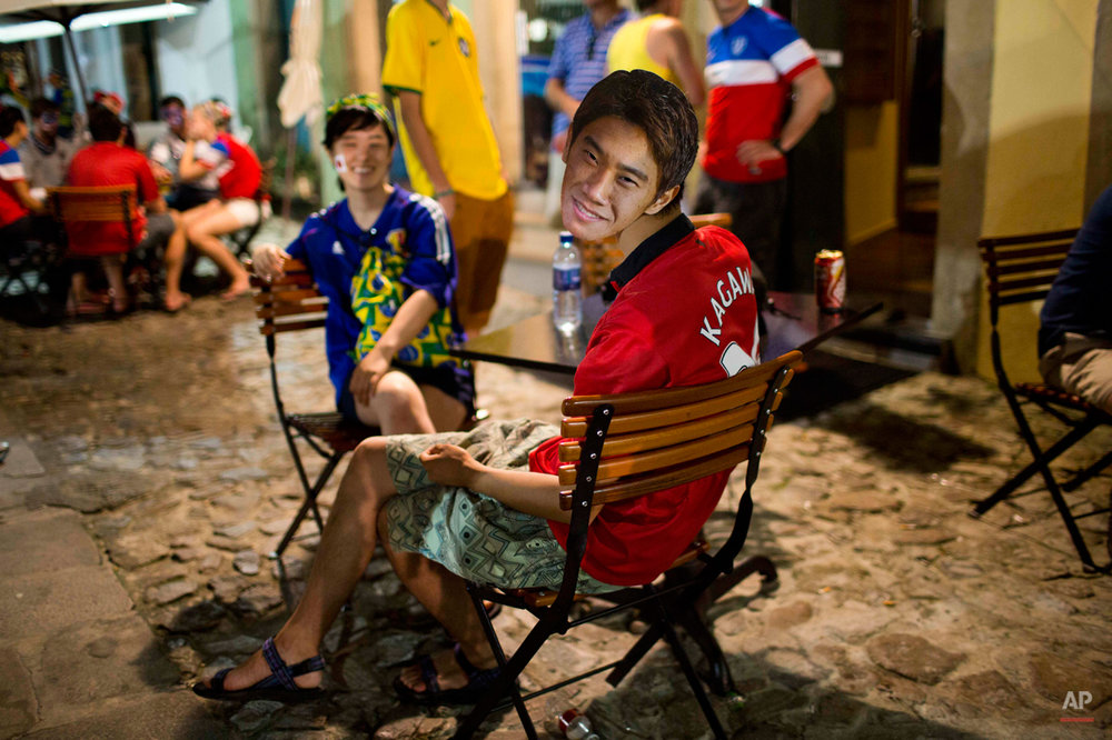 A fan of the Japanese national soccer team sits in a bar wearing a portrait of player Shinji Kagawa in the Pelourinho neighborhood, near the Arena Fonte Nova stadium in Salvador, Brazil, where U.S. and Belgium played a World Cup round of 16 match, Tuesday, July 1, 2014. Belgium beat the United States 2-1 in extra time to reach World Cup quarterfinals. (AP Photo/Rodrigo Abd)