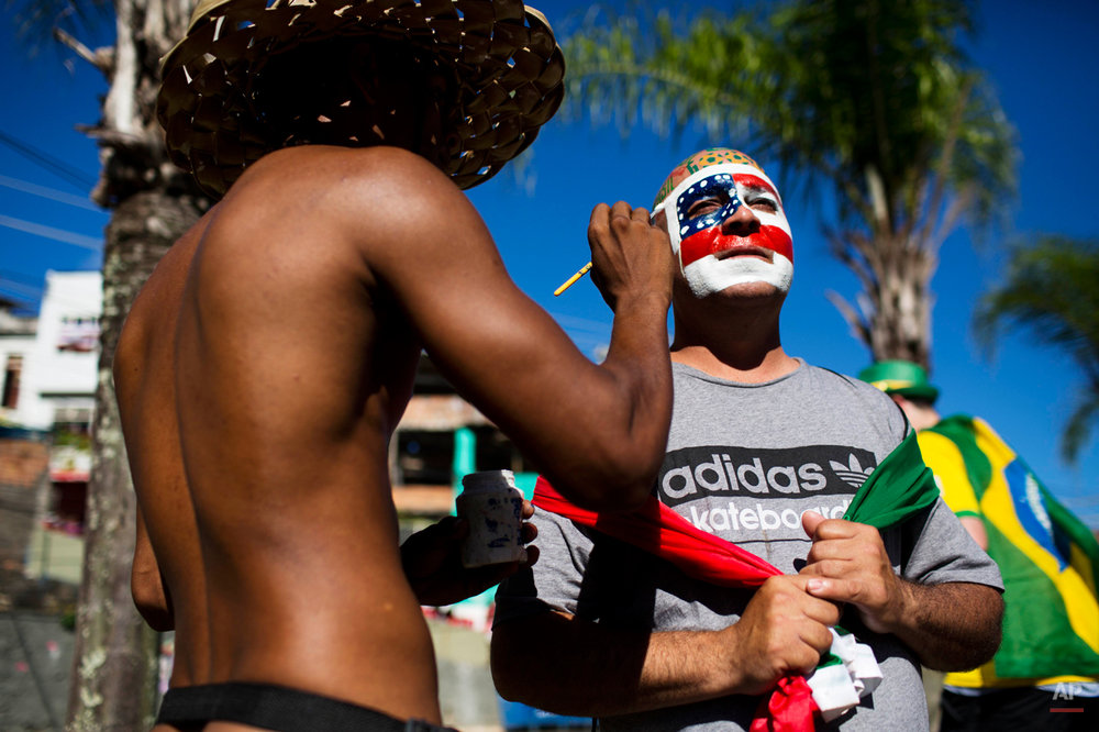 A man paints the United States colors on a soccer fan's face before a World Cup round of 16 match between the U.S. and Belgium outside the Arena Fonte Nova stadium in Salvador, Brazil, Tuesday, July 1, 2014. (AP Photo/Rodrigo Abd)