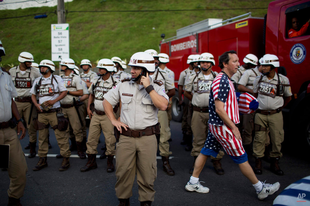 A soccer fan of the U.S. walks amid military policemen standing guard outside the Arena Fonte Nova stadium before World Cup round of 16 match between the U.S. and Belgium in Salvador, Brazil, Tuesday, July 1, 2014. (AP Photo/Rodrigo Abd)
