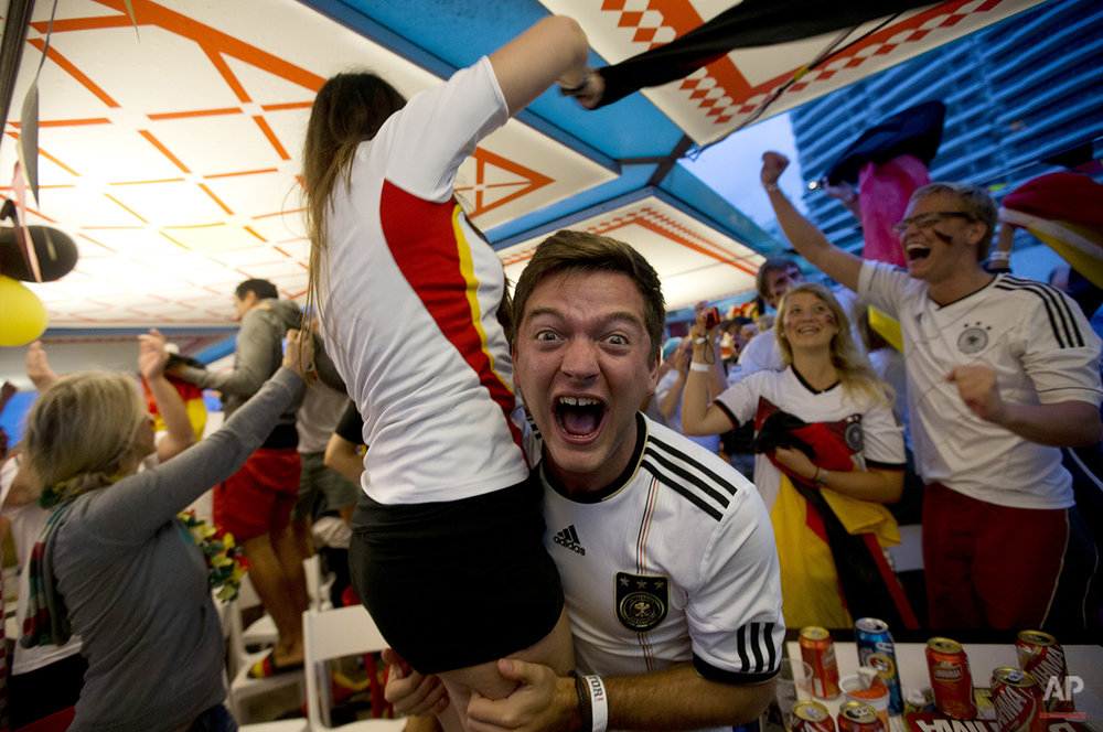 Germany soccer fans celebrate a goal against Brazil as they watch the World Cup semifinal match on Copacabana beach in Rio de Janeiro, Brazil, Tuesday, July 8, 2014. (AP Photo/Silvia Izquierdo)