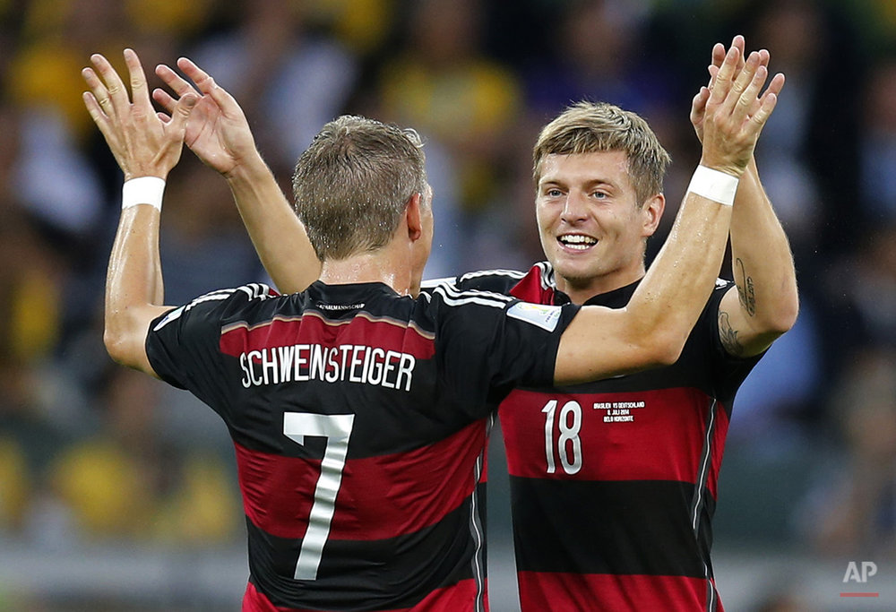 Germany's Bastian Schweinsteiger, left,  Toni Kroos celebrate after scoring during the World Cup semifinal soccer match between Brazil and Germany at the Mineirao Stadium in Belo Horizonte, Brazil, Tuesday, July 8, 2014. (AP Photo/Frank Augstein)