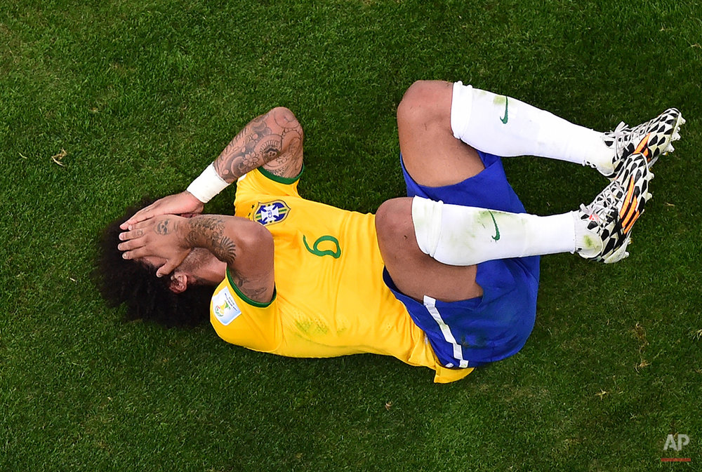 Brazil's Marcelo lies on the pitch during the World Cup semifinal soccer match between Brazil and Germany at the Mineirao Stadium in Belo Horizonte, Brazil, Tuesday, July 8, 2014. (AP Photo/Francois Xavier Marit, Pool)
