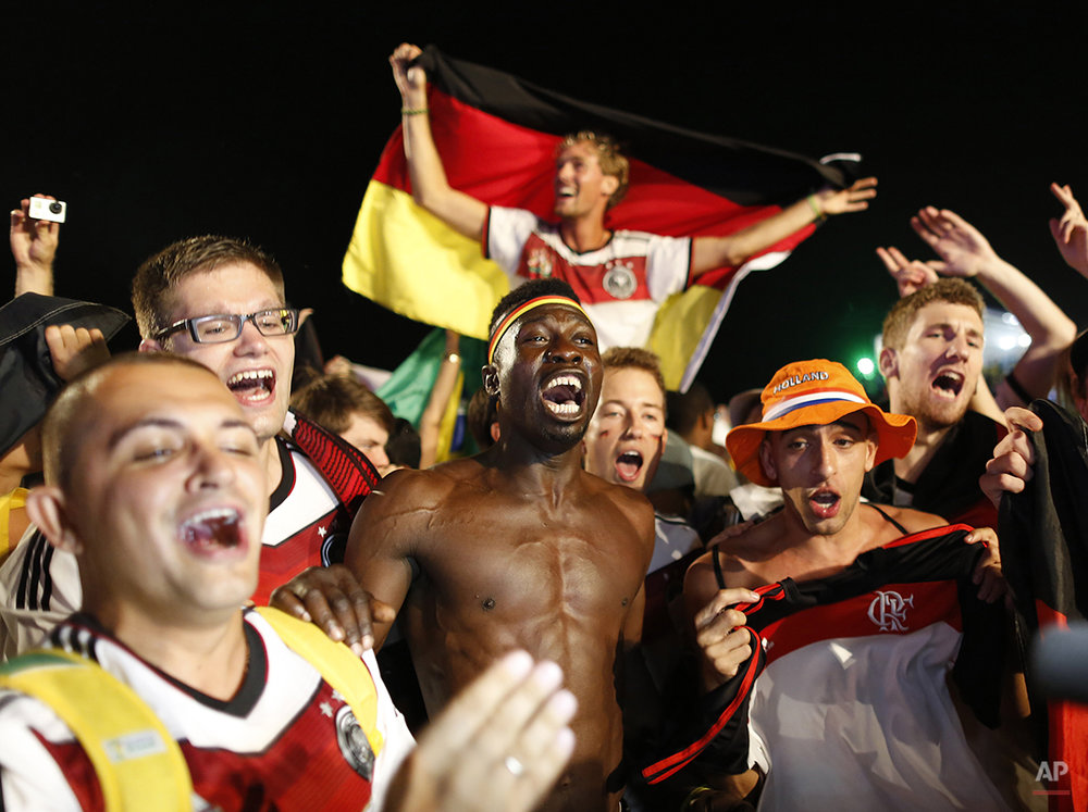 Germany soccer fans celebrate their team's 7-1 victory over Brazil after watching the World Cup semifinal match on a live telecast inside the FIFA Fan Fest area on Copacabana beach in Rio de Janeiro, Brazil, Tuesday, July 8, 2014. (AP Photo/Leo Correa)