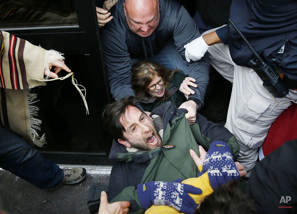 Police scuffle with protesters demonstrating in opposition to the proposed Keystone XL oil pipeline, Monday, March 10, 2014, as they block a door to the federal building in Philadelphia. The protestors say the pipeline would contribute to global warming. (AP Photo/Matt Rourke)