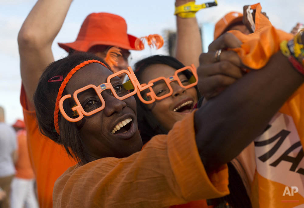 Netherlands soccer fans cheer during a live broadcast of their team's World Cup semifinal match against Argentina inside the FIFA Fan Fest area on Copacabana beach, in Rio de Janeiro, Brazil, Wednesday, July 9, 2014. (AP Photo/Silvia Izquierdo)