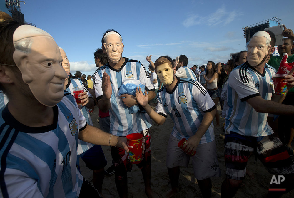 Argentina soccer fans wear masks in the likeness of Pope Francis and Argentina's player Lionel Messi as they attend a live telecast of the World Cup semifinal match between Argentina and Netherlands, inside the FIFA Fan Fest area on Copacabana beach in Rio de Janeiro, Brazil, Wednesday, July 9, 2014. (AP Photo/Silvia Izquierdo)