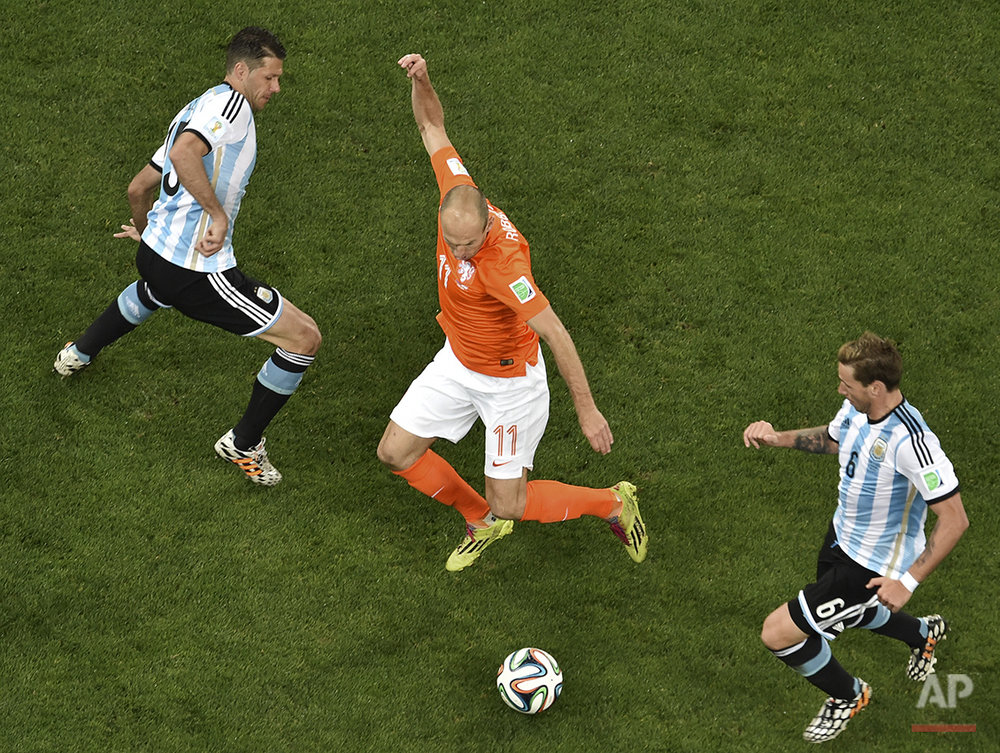 Netherlands' Arjen Robben, center, controls the ball between Argentina's Martin Demichelis, left, and Lucas Bigli, right, during the World Cup semifinal soccer match between the Netherlands and Argentina at the Itaquerao Stadium in Sao Paulo, Brazil, Wednesday, July 9, 2014. (AP Photo/Francois Xavier Marit, Pool)