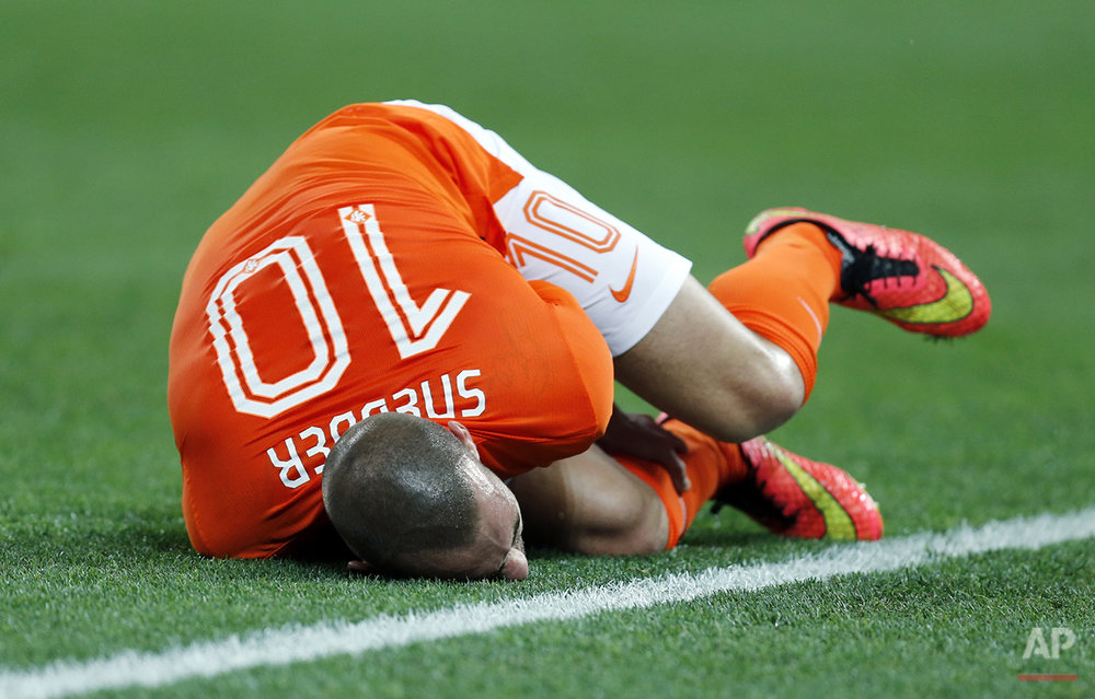 Netherlands' Wesley Sneijder holds his leg after a foul during the World Cup semifinal soccer match between the Netherlands and Argentina at the Itaquerao Stadium in Sao Paulo, Brazil, Wednesday, July 9, 2014. (AP Photo/Frank Augstein)