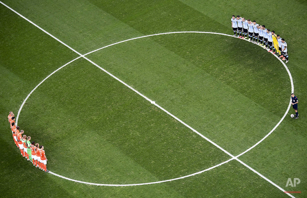 Players from the Netherlands, left, and Argentina, right, observe a minute of silence to honor the death of Argentine soccer legend Alfredo di Stefano prior to their World Cup semifinal soccer match at the Itaquerao Stadium in Sao Paulo, Brazil, Wednesday, July 9, 2014. (AP Photo/Francois Xavier Marit, Pool)