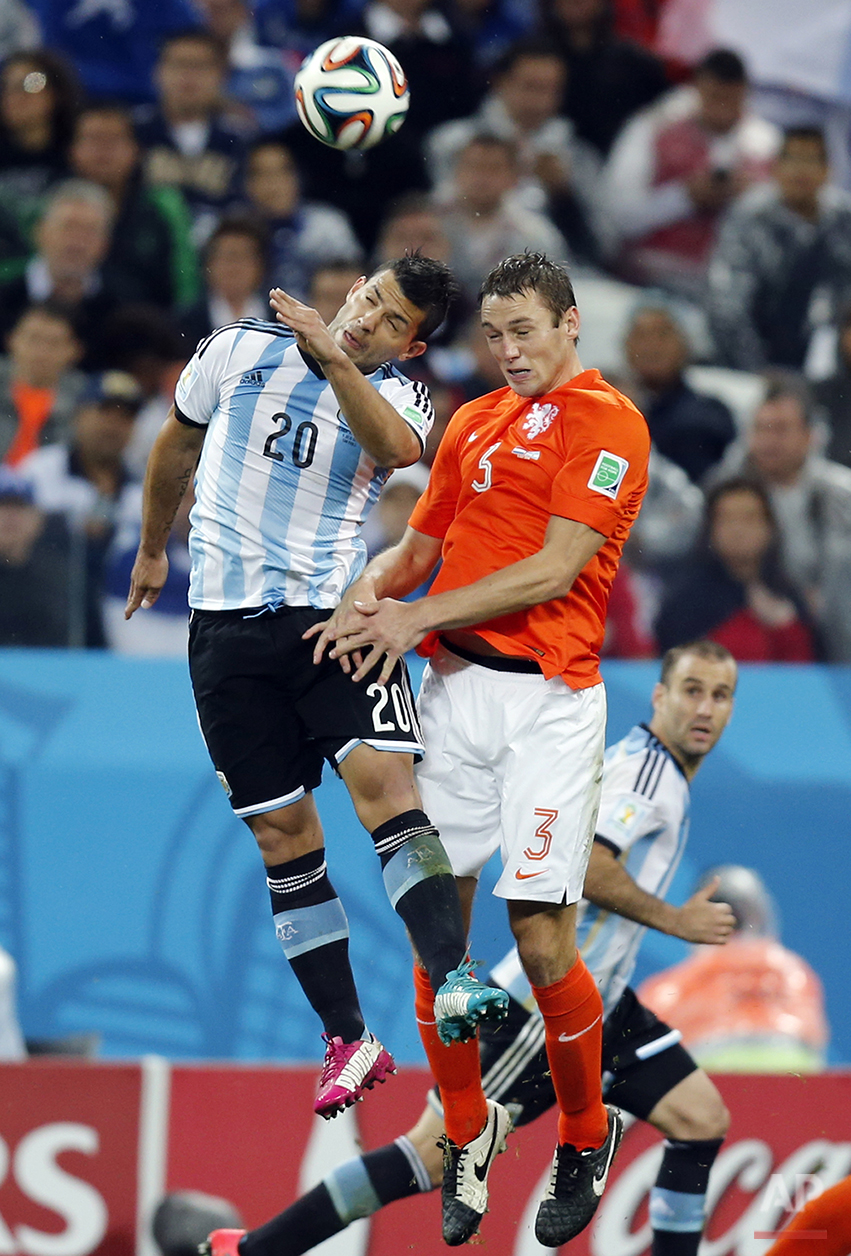 Argentina's Sergio Aguero, left, and Netherlands' Stefan de Vrij go for a header during the World Cup semifinal soccer match between the Netherlands and Argentina at the Itaquerao Stadium in Sao Paulo, Brazil, Wednesday, July 9, 2014. (AP Photo/Frank Augstein)