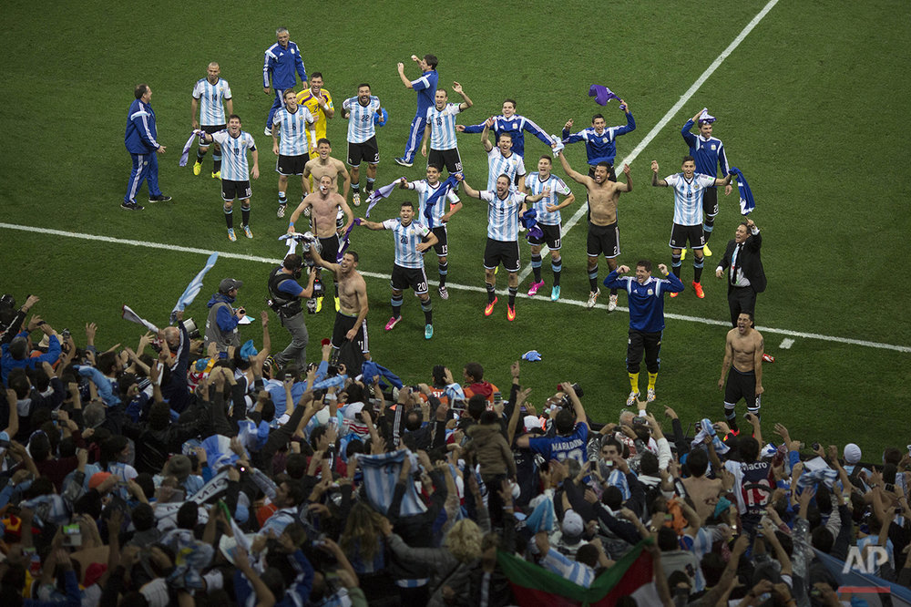 Argentina soccer players celebrate with fans after defeating the Netherlands during a World Cup semifinal soccer match at the Itaquerao Stadium in Sao Paulo Brazil, Wednesday, July 9, 2014.  Argentina reached the World Cup final on Wednesday after beating the Netherlands 4-2 in a penalty shootout. (AP Photo/Felipe Dana)
