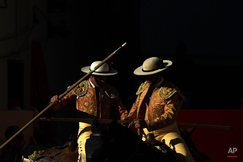"A couple of picadors, horsemen with a spear that participates in a bullfight, wait before a bullfight of the San Fermin festival, in Pamplona, Spain, Monday, July 7, 2014. Revelers from around the world arrive in Pamplona every year to take part on some of the eight days of the running of the bulls glorified by Ernest Hemingway's 1926 novel ""The Sun Also Rises."" (AP Photo/Daniel Ochoa de Olza)"