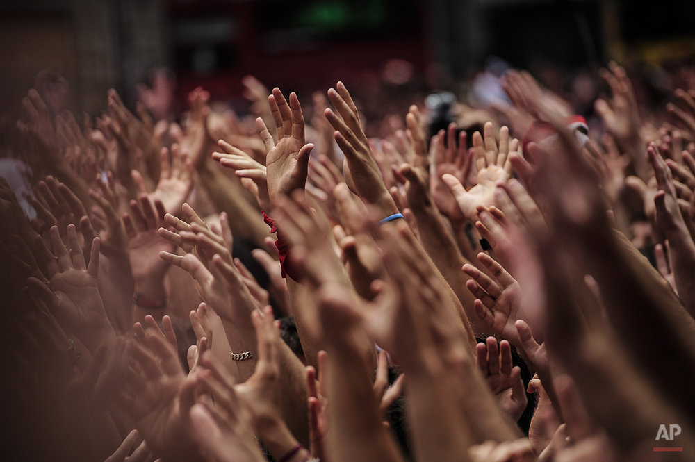 "Revelers hold up their hands during the launch of the 'Chupinazo' rocket, to celebrate the official opening of the 2014 San Fermin fiestas, in Pamplona, Spain, Sunday, July 6, 2014. Revelers from around the world kick off the festival with a messy party in the Pamplona town square, one day before the first of eight days of the running of the bulls glorified by Ernest Hemingway's 1926 novel ""The Sun Also Rises."" (AP Photo/Alvaro Barrientos)"