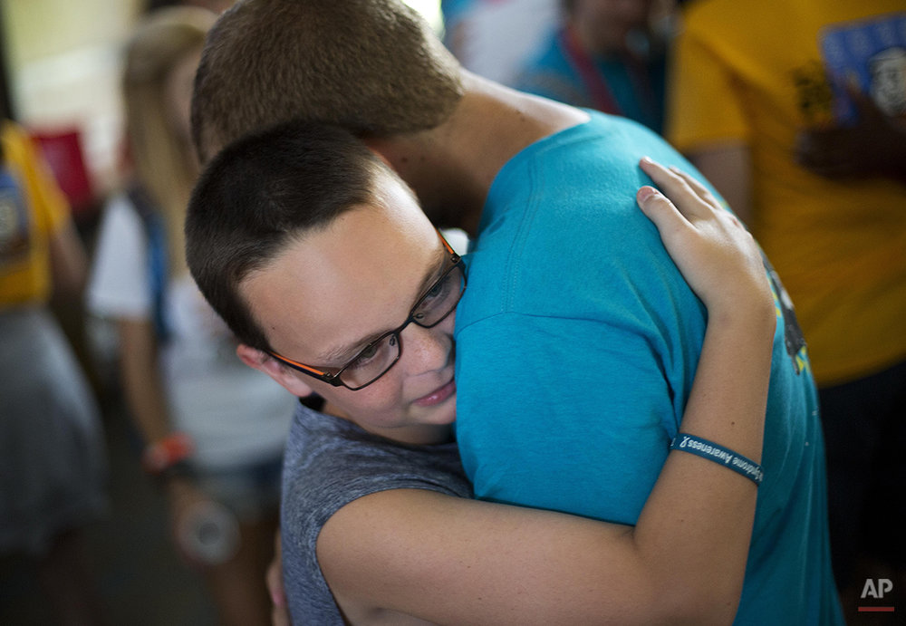 In this July 18, 2014 photo, counselor Paul Luongo, 24, right, says goodbye to camper Colton Semonasky, 12, of Leesburg, Fla., as they leave to go home from Camp Twitch and Shout, a camp for children with Tourette Syndrome in Winder, Ga. (AP Photo/David Goldman)