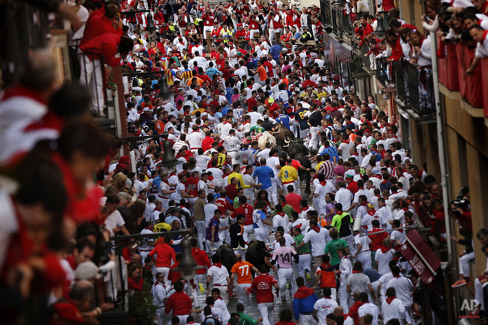 "Revelers are chased by Dolores Aguirre's ranch fighting bulls during the running of the bulls of the San Fermin festival, in Pamplona, Spain, Tuesday, July 8, 2014. Revelers from around the world arrive in Pamplona take part in the eight-day running of the bulls glorified by Ernest Hemingway's 1926 novel ""The Sun Also Rises."" (AP Photo/Daniel Ochoa de Olza)"