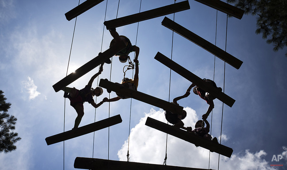 In this July 15, 2014 photo, campers cross an elevated obstacle rope course holding hands to encourage team building skills at Camp Twitch and Shout, a camp for children with Tourette Syndrome in Winder, Ga. (AP Photo/David Goldman)