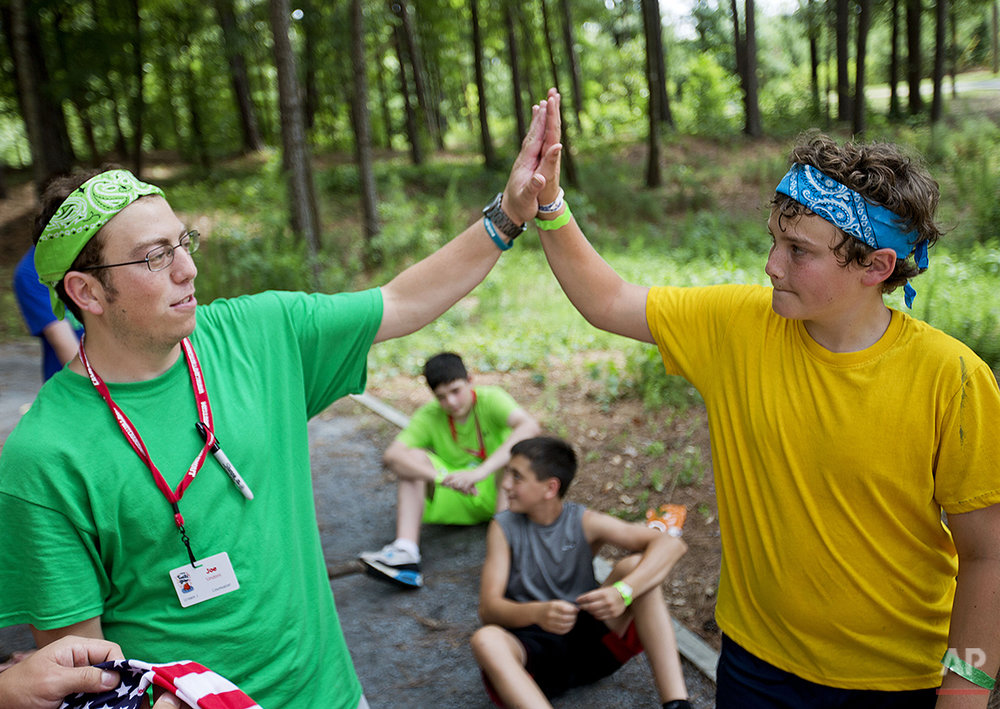 In this July 15, 2014 photo, Logan Henderson, 13, of Blairsville, Ga., right, is high-fived by counselor Joe Sindoni, 25, after completing a rope course in the trees at Camp Twitch and Shout, a camp for children with Tourette Syndrome in Winder, Ga. (AP Photo/David Goldman)