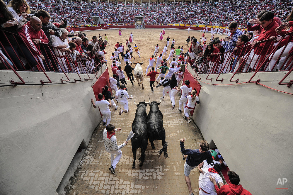 "Revelers arrive at the bull ring beside ''Dolores Aguirre Ybarra'' fighting bulls during the running of the bulls at the San Fermin festival, in Pamplona, Spain, Tuesday, July 8, 2014. Revelers from around the world arrive to Pamplona every year to take part in some of the eight days of the running of the bulls glorified by Ernest Hemingway's 1926 novel ""The Sun Also Rises."" (AP Photo/Alvaro Barrientos)"