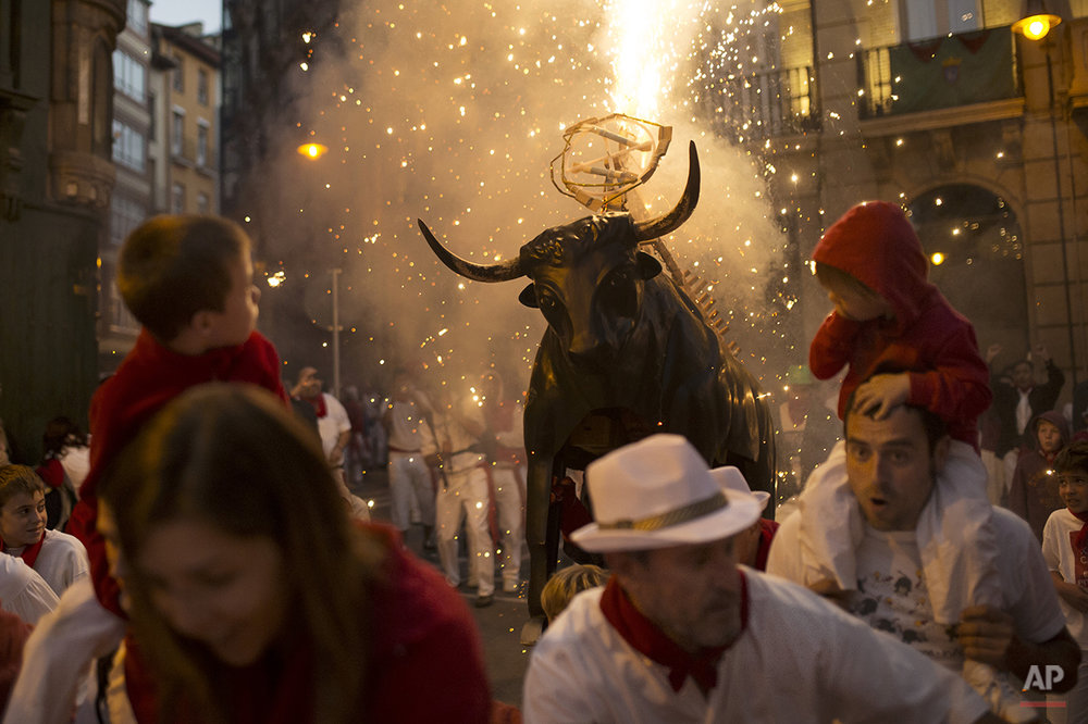 "Revelers run away followed by a flaming fake bull ""Toro de fuego"" during the second day of the 2014 San Fermin fiestas in Pamplona, Spain, Monday, July 7, 2014. Revelers from around the world arrive to Pamplona every year to take part on some of the eight days of the running of the bulls glorified by Ernest Hemingway's 1926 novel ""The Sun Also Rises."" (AP Photo/Andres Kudacki)"