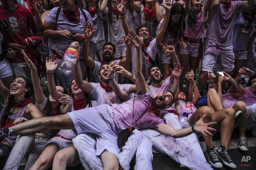 "Revelers celebrate during the launch of the 'Chupinazo' rocket, to celebrate the official opening of the 2014 San Fermin fiestas, in Pamplona, Spain, Sunday, July 6, 2014. Revelers from around the world kick off the festival with a messy party in the Pamplona town square, one day before the first of eight days of the running of the bulls glorified by Ernest Hemingway's 1926 novel ""The Sun Also Rises."" (AP Photo/Alvaro Barrientos)"