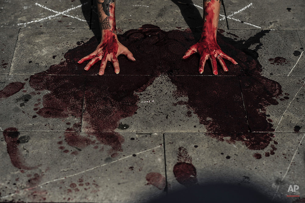 Hands of an anti-bullfighting demonstrator covered with blood are seen during a protest against the bull runs, on the Ayuntamiento Square in Pamplona northern Spain, Saturday, July 5, 2014. On July 6, the San Fermin festival will begin with the ''txupinazo'' , the opening ceremony with people participating in bull runs, music and dance, through the old street of the city. (AP Photo/Alvaro Barrientos)