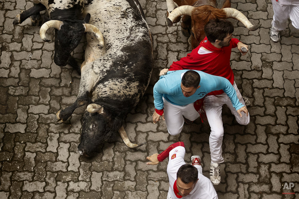"Revelers run with Torrestrella ranch fighting bulls during the running of the bulls of the San Fermin festival, in Pamplona, Spain, Monday, July 7, 2014. Revelers from around the world arrive in Pamplona every year to take part on some of the eight days of the running of the bulls glorified by Ernest Hemingway's 1926 novel ""The Sun Also Rises."" (AP Photo/Daniel Ochoa de Olza)"