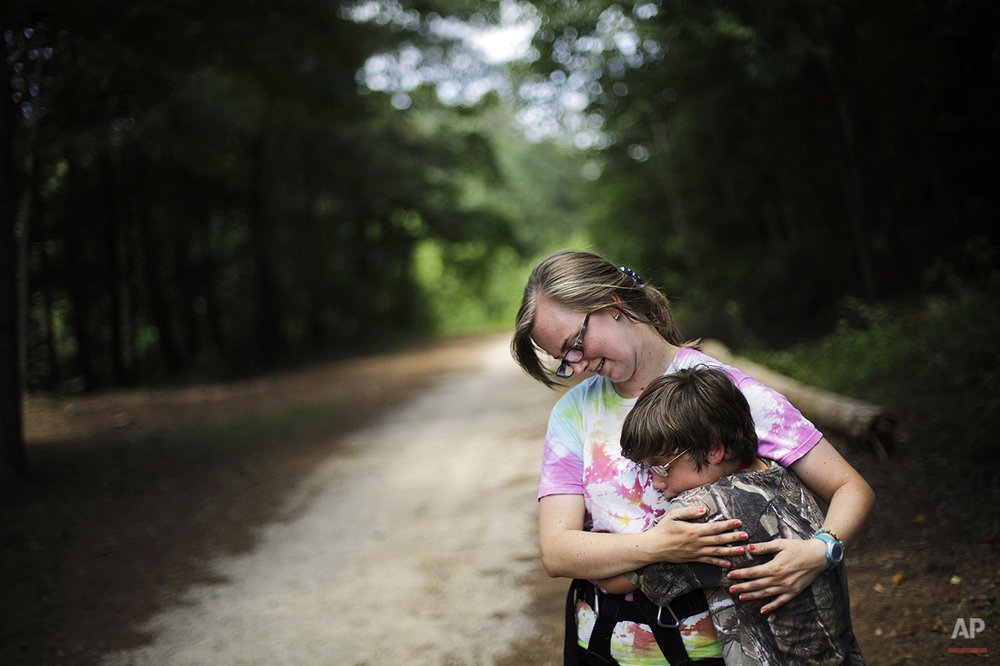 "In this July 15, 2014 photo, Liam Harrison, 13, of Nashville, Tenn., right, embraces camp worker Katie Lesesne, 21, while experiencing a tic where he feels the urge to hug someone in proximity at Camp Twitch and Shout, a camp for children with Tourette Syndrome in Winder, Ga. ""When I get the feeling, I just want to squeeze someone,"" explains Harrison. ""When I let go it makes me happy. It feels so awesome like I'm gaining something. It makes me feel a lot better."" (AP Photo/David Goldman)"