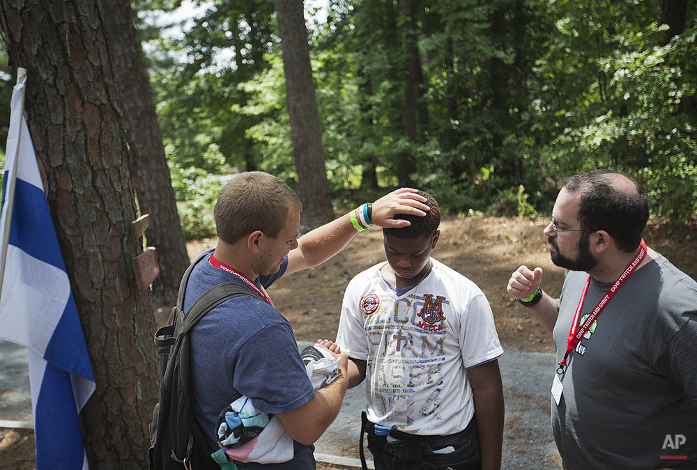 In this July 15, 2014 photo, Lazarus Jordan, 13, of Long Beach, Calif, center, is congratulated by counselors Paul Luongo, 24, left, and Seth Tucker, 29, after completing a rope course in the trees at Camp Twitch and Shout, a camp for children with Tourette Syndrome in Winder, Ga. The weeklong summer camp helps children embrace and cope with the neurological disorder that makes people have different types of involuntary muscle movements or speech known as tics. Many of the counselors also have Tourette's and the tics range from mild to severe. Through sharing experiences, the children learn to better cope with Tourette's while forming strong friendships. For many, the biggest challenge is leaving. (AP Photo/David Goldman)