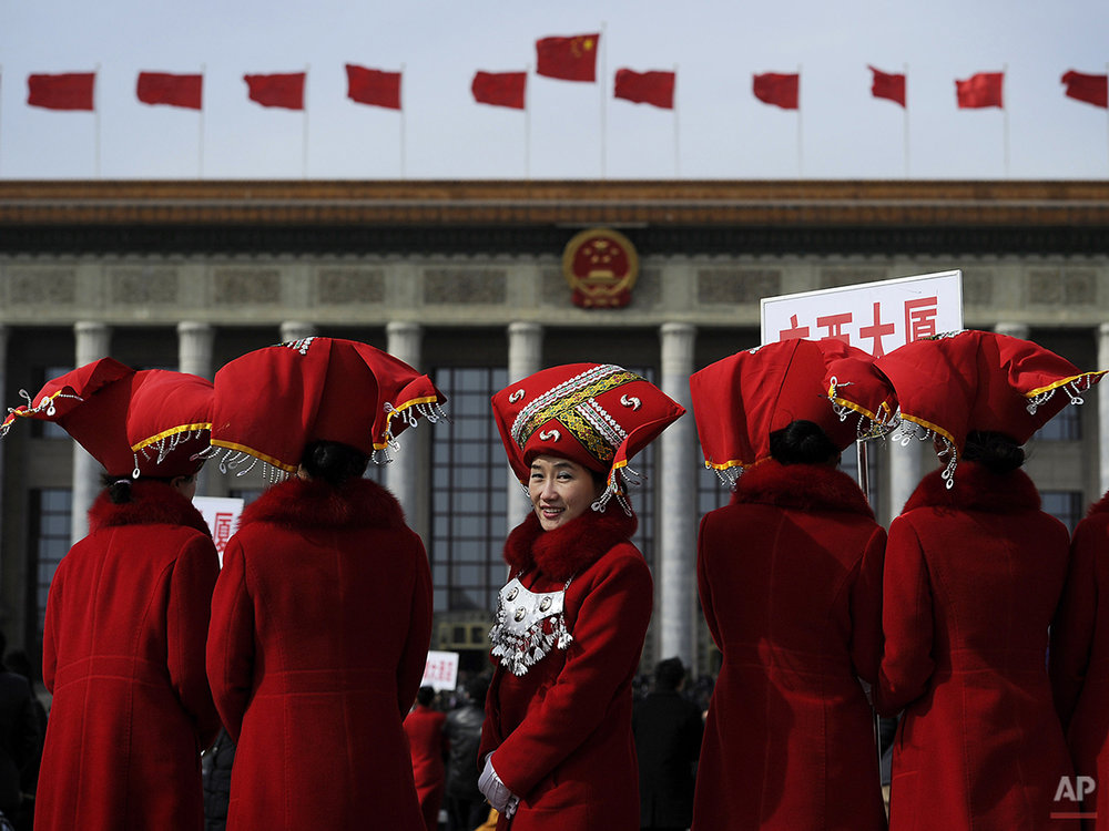 A Chinese usher in ethnic headwear, center, look back as they pose for photograph on the Tiananmen Square during the opening session of the National People's Congress at the Great Hall of the People in Beijing, Friday, March 5, 2010. (AP Photo/Andy Wong)