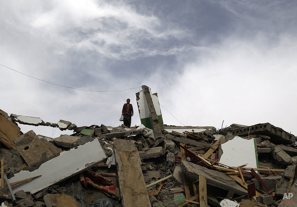 A Tibetan woman stands on top a collapsed building in Yushu County, northwest China's Qinghai province, Friday, April 16 , 2010. Armed with life detectors, rescuers searched for survivors Friday more than 48 hours after an earthquake leveled homes in western China, killing at least 760 people. (AP Photo/Andy Wong)
