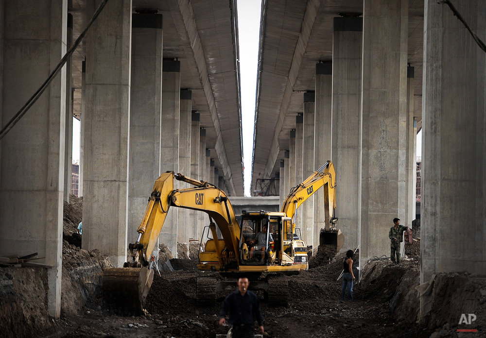 Chinese workers labor below the site of an under construction highway in Tianjin, China Thursday, Aug. 5, 2010. China is set to overtake Japan as the world's second largest-economy in a resurgence that is changing everything from the global balance of military and financial power to how cars are designed. (AP Photo/Andy Wong)