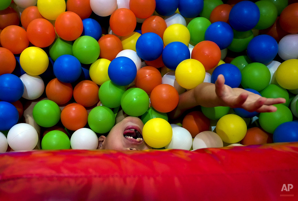A child plays on an inflatable balloon bouncer fill with balls set up by an exhibitor during the Kids Fun Expo in Beijing, China Thursday, July 25, 2013. (AP Photo/Andy Wong)