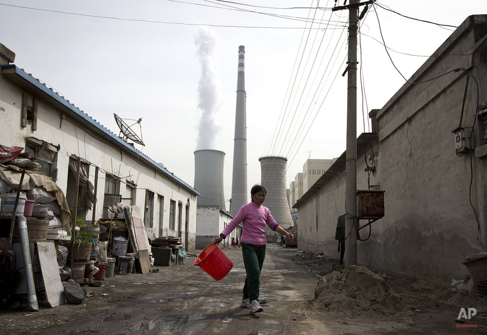 A woman walks through a neighborhood near a coal-fired power plant in Beijing on Friday, April 12, 2013. China, the world's largest producer of carbon dioxide, is directly feeling the man-made heat of global warming, scientists conclude in the first study to link the burning of fossil fuels to one country's rise in its daily temperature spikes. (AP Photo/Andy Wong)