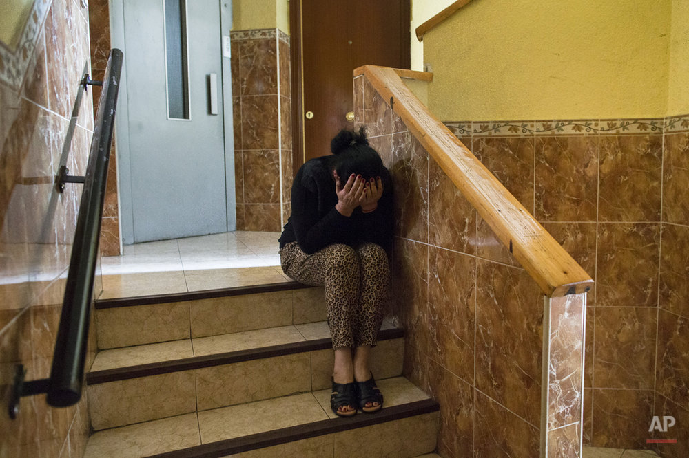 Carmen Escudero Garcia, 59 years old, cries as she waits for the police to evict her son, Jose Garcia Escudero, 39, and his family in Madrid, Spain, Monday, May 19, 2014. Escudero and his 30 year old wife Raquel de Cadiz Escudero, have 5 children and they occupied a Banco Popular bank apartment over a year ago and they cannot afford to pay the rent with a low income of 600 euros ($823) a month. The apartment has been sold to an investor group that now demands the eviction of the family. The eviction was postponed for 9 days with the help of housing rights activists. (AP Photo/Andres Kudacki)