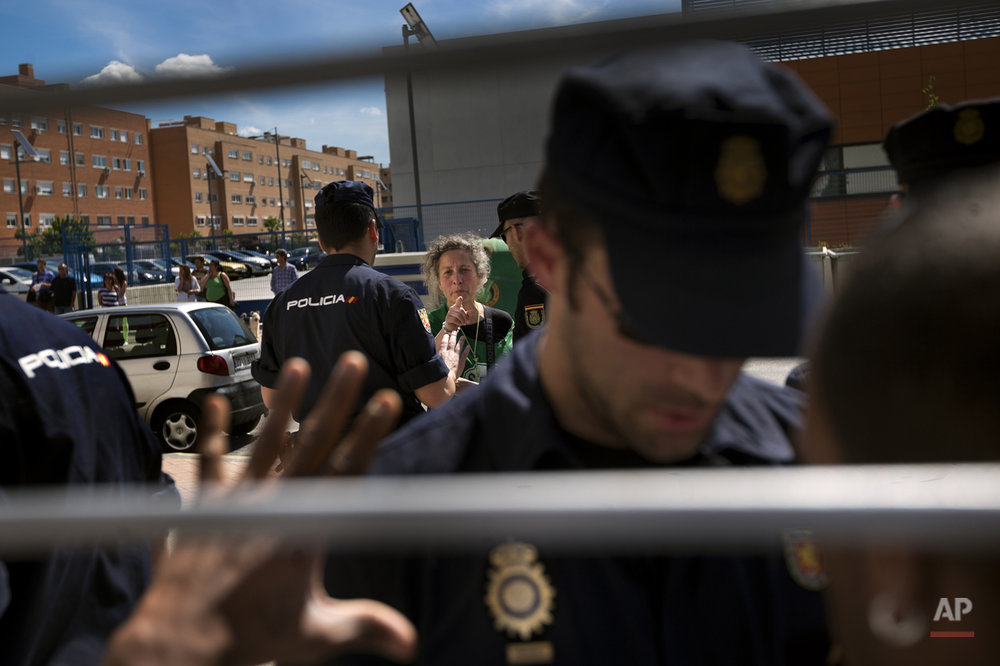 Veronica Carro Cabaninas, 51 years old, born in Argentina and with Spanish citizenship speaks with police officers before her eviction from her house, in Parla, Spain, Wednesday, April 30, 2014. Veronica, a former gardener and concierge at Parla's townhall, has resided in the apartment with her 14 year old daughter Rocio for the past 5 years, but since being unemployed for the last 3 years and her only income was a state handout of 426 euros ($584) a month she could not afford to pay a protected rent of 370 euros a month ($513) to Lazora, a private investor company who bought her house from the City Hall Housing and Land Company (EMVS). Lazora demanded their eviction. (AP Photo/Daniel Ochoa de Olza)