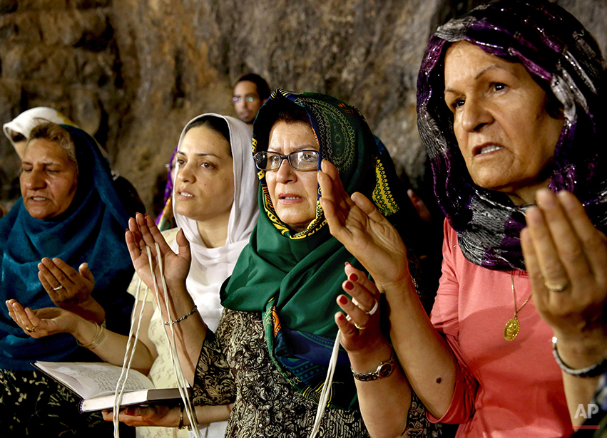 In this Friday, June 13, 2014 photo, Zoroastrians pray in Chak Chak, a mountain shrine, some 600 kilometers (370 miles) southeast of the capital Tehran, Iran. At Chak Chak, some 600 kilometers (370 miles) southeast of the capital Tehran, believers gathered to remember Nikbanou, a heroine of the faith who according to tradition took shelter in the mountain and prayed for help. Miraculously, the mountain was said to have opened up and given protection to the princess, the youngest daughter of the last king of the Persian Sassanian empire. (AP Photo/Ebrahim Noroozi)